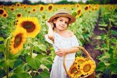 Menina em um vestido branco, um chapéu de palha com uma cesta completa dos girassóis sorrindo na câmera em um campo de fotos de stock