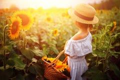 Menina em um vestido branco, um chapéu de palha com uma cesta completa dos girassóis sorrindo na câmera em um campo de fotografia de stock