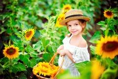 Menina em um vestido branco, um chapéu de palha com uma cesta completa dos girassóis sorrindo na câmera em um campo de foto de stock royalty free