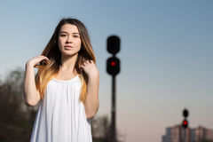 A menina em um vestido branco e dobra seu cabelo contra a lanterna vermelha Fotografia de Stock Royalty Free