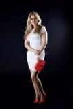 Menina em um vestido branco, em umas sapatas vermelhas e em um saco de embreagem vermelho Imagens de Stock Royalty Free