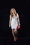 Menina em um vestido branco, em umas sapatas vermelhas e em um saco de embreagem vermelho Foto de Stock