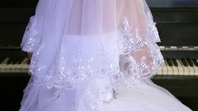 A menina em um vestido branco joga o piano A noiva executa uma parte de m?sica no piano Ind?stria musical vídeos de arquivo