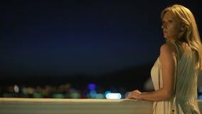 Menina em um vestido branco longo caminhadas ao longo da praia na noite filme