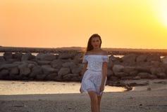Menina em um vestido branco no por do sol fotos de stock