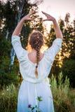 A menina em um vestido branco olha o por do sol na floresta respira e relaxa Mulher com penteado da trança que pensa sobre a natu fotografia de stock royalty free