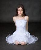 A menina em um vestido branco senta-se em um fundo preto Foto de Stock Royalty Free