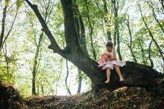 A menina em um vestido com boneca senta-se em uma árvore na floresta Fotografia de Stock Royalty Free