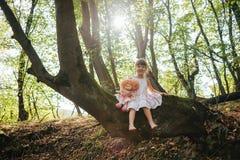 A menina em um vestido com boneca senta-se em uma árvore na floresta Imagens de Stock Royalty Free