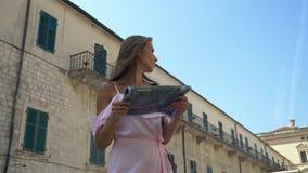 Menina em um vestido cor-de-rosa com um mapa vídeos de arquivo