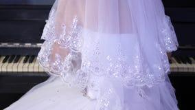 A menina em um vestido de bola branco joga o piano A noiva executa uma parte de m?sica no piano Ind?stria musical vídeos de arquivo