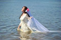 A menina em um vestido de casamento na água Imagens de Stock Royalty Free