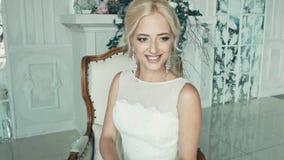 A menina em um vestido de casamento que sorri e que olha dum lado ao outro video estoque