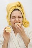 A menina em um vestido de molho morde um limão Fotos de Stock Royalty Free