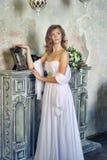 menina em um vestido de noite branco que está pela chaminé Fotografia de Stock Royalty Free