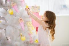 A menina em um vestido elegante decora a árvore de Natal Fotos de Stock Royalty Free