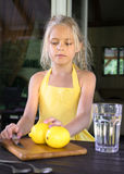 Menina em um vestido, em um limão e em uma limonada amarelos Foto de Stock