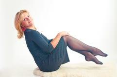 A menina em um vestido escuro senta o mantimento para os pés Foto de Stock