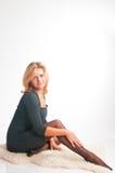 A menina em um vestido escuro senta o mantimento para os pés Fotografia de Stock
