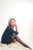 A menina em um vestido escuro senta-se Fotografia de Stock Royalty Free