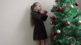 A menina em um vestido marrom seleciona o lugar na árvore de Natal verde pendurando uma bola vermelha sob a forma dos ornamento vídeos de arquivo