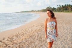 Menina em um vestido na praia perto do oceano Imagens de Stock Royalty Free