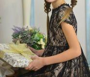 A menina em um vestido preto está guardando um presente abra presentes de aniversário fotos de stock royalty free