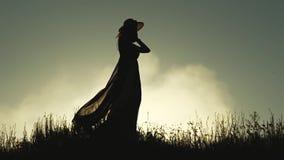 Menina em um vestido que anda no vento no campo Movimento lento Silhueta filme