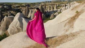 A menina em um vestido roxo longo está alta em uma rocha em Cappadocia filme