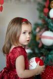 Menina em um vestido vermelho a árvore de Natal Fotos de Stock Royalty Free