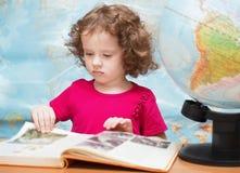 A menina em um vestido vermelho está lendo um livro fotografia de stock royalty free