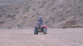 A menina em uma bicicleta do quadril?tero monta atrav?s do deserto de Egito filme