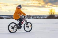 A menina em uma bicicleta no inverno monta no gelo contra um fundo de Fotos de Stock Royalty Free