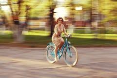 Menina em uma bicicleta no movimento Imagens de Stock