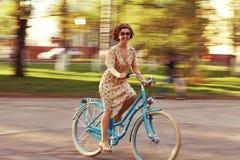 Menina em uma bicicleta no movimento Fotografia de Stock Royalty Free