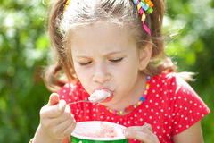 Menina em uma blusa vermelha com apreciação que come o gelado Imagens de Stock Royalty Free