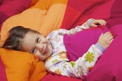 Menina em uma cama Fotos de Stock