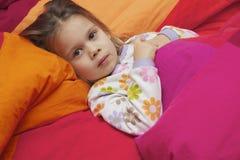 Menina em uma cama Imagens de Stock Royalty Free