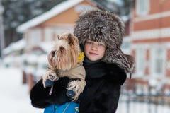 Menina em uma caminhada gelado da tarde do inverno do chapéu forrado a pele com seu yorkshire terrier amado do cão imagem de stock