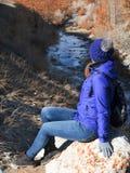 A menina em uma caminhada nas montanhas sentou-se para baixo para descansar em uma pedra e olhou-se o rio congelado imagens de stock royalty free