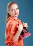 Menina em uma camisa alaranjada e em calças de brim com o saco de compras no vagabundos azuis fotos de stock