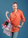 Menina em uma camisa alaranjada e em calças de brim com sacos de compras em um b azul fotografia de stock royalty free