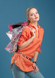 Menina em uma camisa alaranjada e em calças de brim com sacos de compras em um b azul imagem de stock