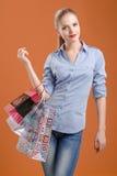 Menina em uma camisa azul e em calças de brim com sacos de compras imagens de stock royalty free