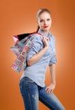 Menina em uma camisa azul e em calças de brim com sacos de compras imagem de stock royalty free
