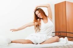 Menina em uma camisa branca que encontra-se nas folhas na cama em casa Imagem de Stock Royalty Free