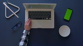 A menina em uma camisa cinzenta está datilografando em um portátil ao sentar-se na tabela e no café bebendo o telefone e os vidro vídeos de arquivo