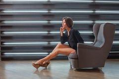 Menina em uma camisa do ` s do homem negro em sua cadeira Fotografia de Stock Royalty Free