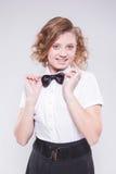 A menina em uma camisa e em um laço brancos olha a câmera e o smilin imagens de stock royalty free