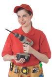 A menina em uma camisa vermelha com ferramentas e uma broca fotografia de stock royalty free